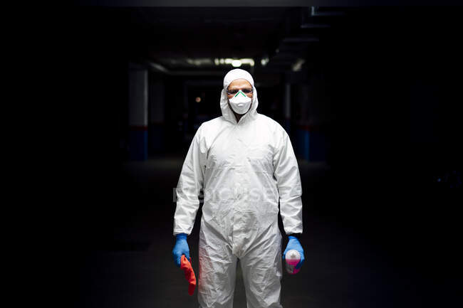 Personal de limpieza en traje con desinfectante y paño de limpieza - foto de stock