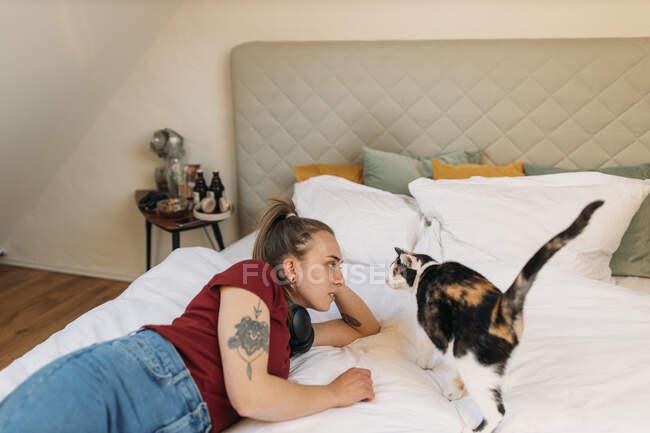 Mujer joven acostada en la cama en casa con gato - foto de stock