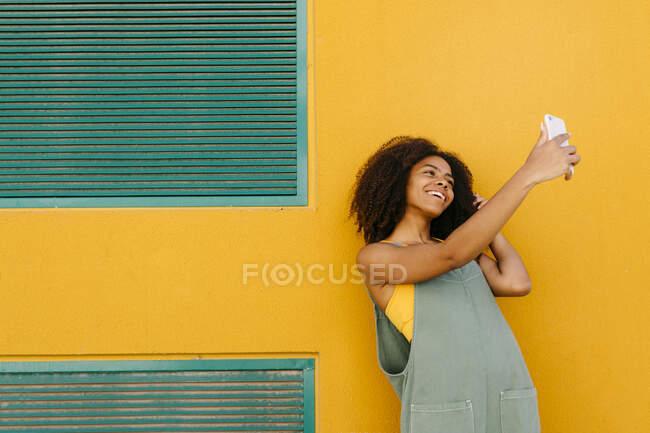 Портрет щасливої молодої жінки, одягненої в комбінезон перед жовтою стіною, робить селфі. — стокове фото