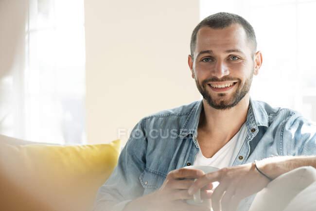 Retrato de jovem feliz em casa segurando caneca de café — Fotografia de Stock