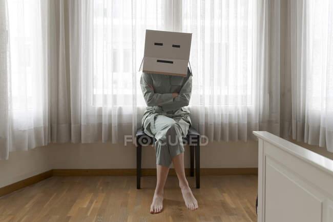 Mujer con una caja de cartón en la cabeza con sonrisa aburrida sentada en la silla con los brazos cruzados - foto de stock