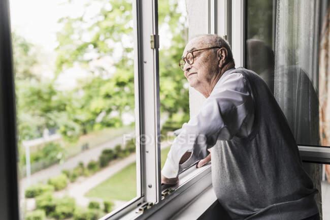 Homem sênior olhando pela janela — Fotografia de Stock