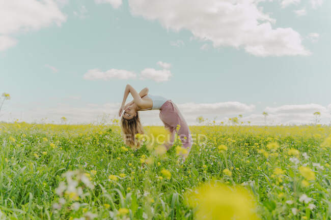 Young woman bending over backwards in a flower meadow in spring — стокове фото
