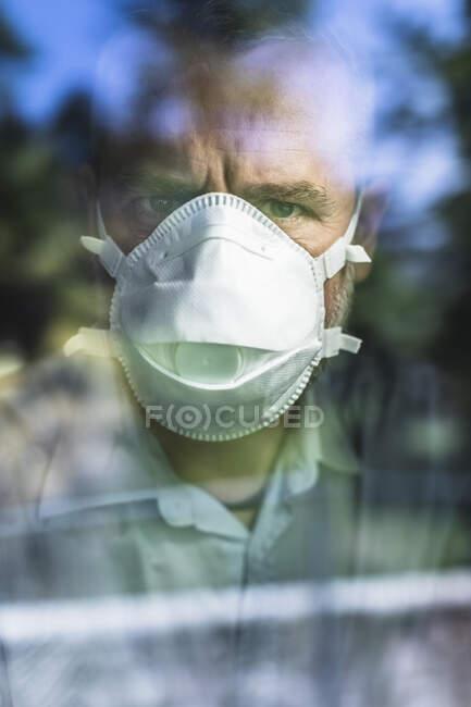 Hombre maduro con máscara protectora mirando por la ventana, mirando a la cámara - foto de stock