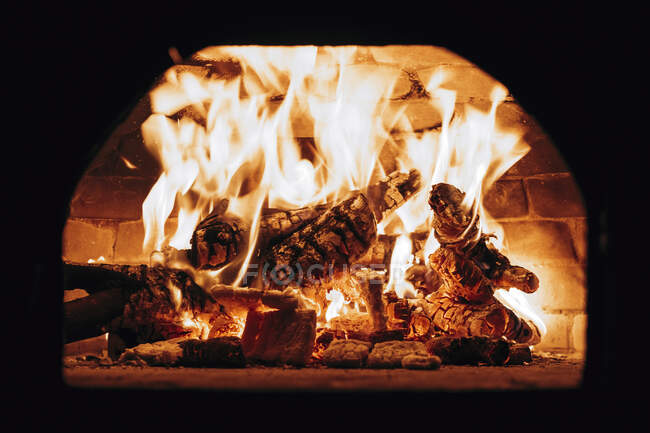 Firewood burning in pizza oven — Stock Photo