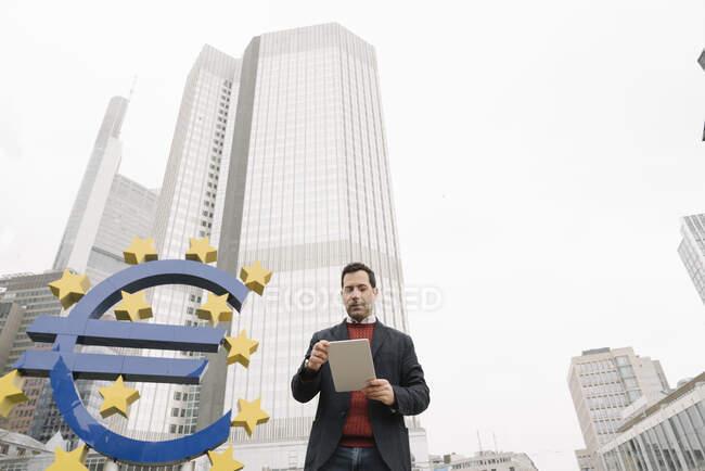 Uomo d'affari che utilizza tablet digitale contro scultura e Banca centrale europea a Francoforte, Germania — Foto stock