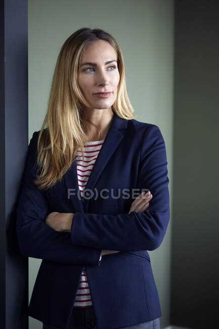 Portrait of businesswoman leaning against a wall looking sideways — Stock Photo