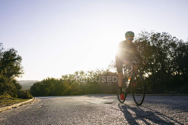 Спортсмен на велосипеде по проселочной дороге на закате — стоковое фото