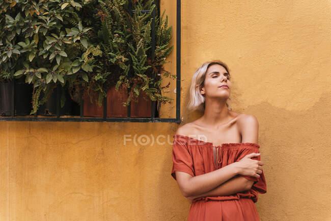Портрет молодої жінки з закритими очима перед жовтою стіною. — стокове фото