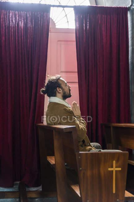 Hombre rezando en una iglesia - foto de stock