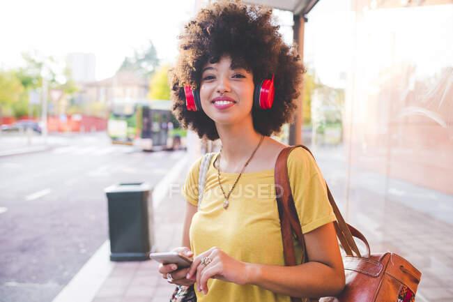 Jovencita feliz con peinado afro escuchando música con auriculares en la ciudad - foto de stock