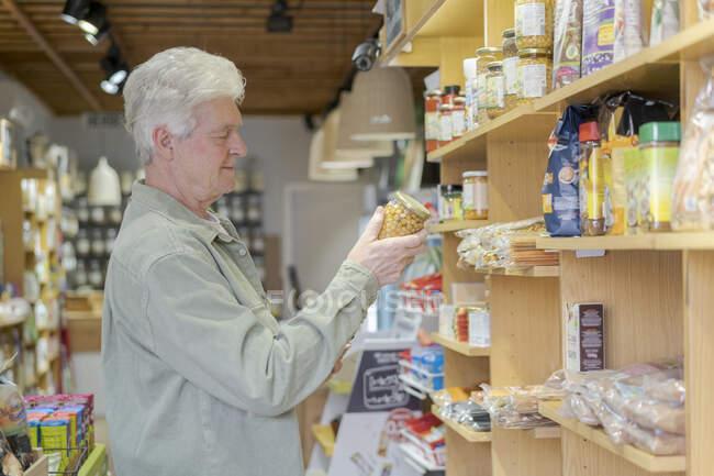 Старший покупает продукты в небольшом продуктовом магазине — стоковое фото