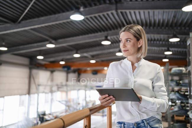 Посмішка молодої жінки, яка користується планшетом на заводі. — стокове фото
