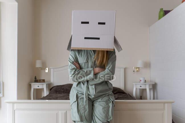Mujer con una caja de cartón en la cabeza con sonrisa aburrida apoyada en la cama en casa - foto de stock