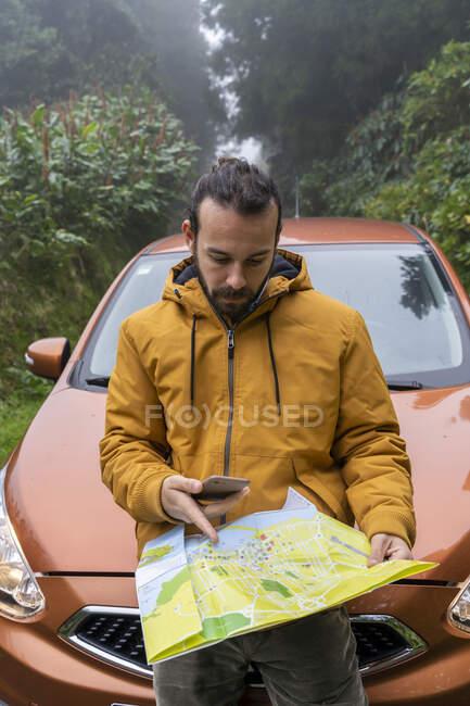 Uomo con smartphone e mappa fuori dall'auto sulla strada forestale, Isola di Sao Miguel, Azzorre, Portogallo — Foto stock