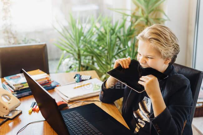 Chico enojado sentado en el escritorio mordiendo en la tableta - foto de stock