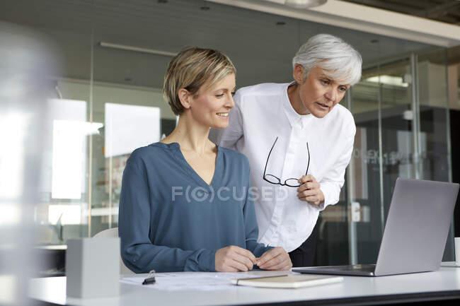 Дві бізнесмени працюють разом з ноутбуком у офісі. — стокове фото