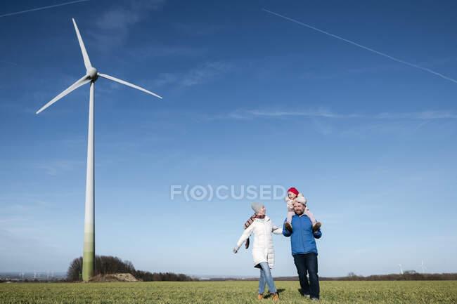 Pais felizes com a filhinha andando em um campo com roda de vento no fundo — Fotografia de Stock