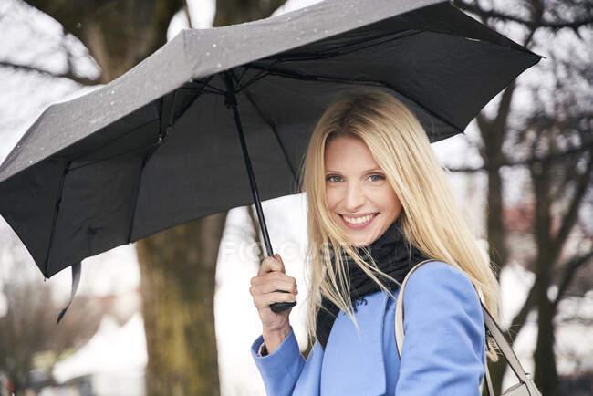 Портрет усміхненої блондинки, що тримає парасольку на відкритому повітрі. — стокове фото