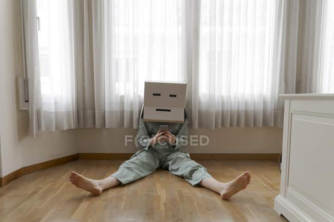 Mujer con una caja de cartón en la cabeza con sonrisa aburrida sentada en el suelo y usando un teléfono inteligente - foto de stock