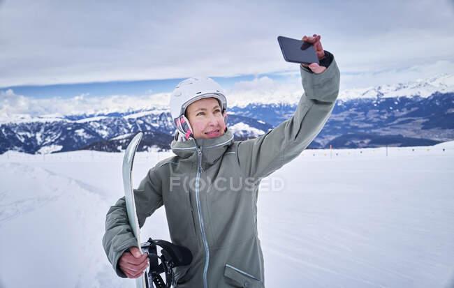 Sorridente snowboard femminile scattare un selfie con il suo smartphone — Foto stock
