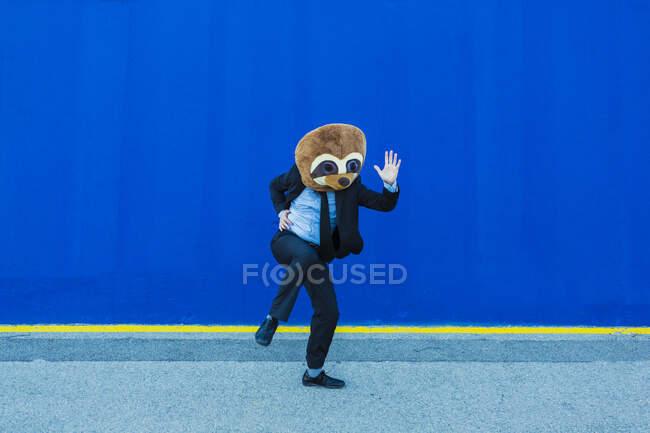Бізнесмен у чорному костюмі з масками суконь танцює перед синьою стіною. — стокове фото