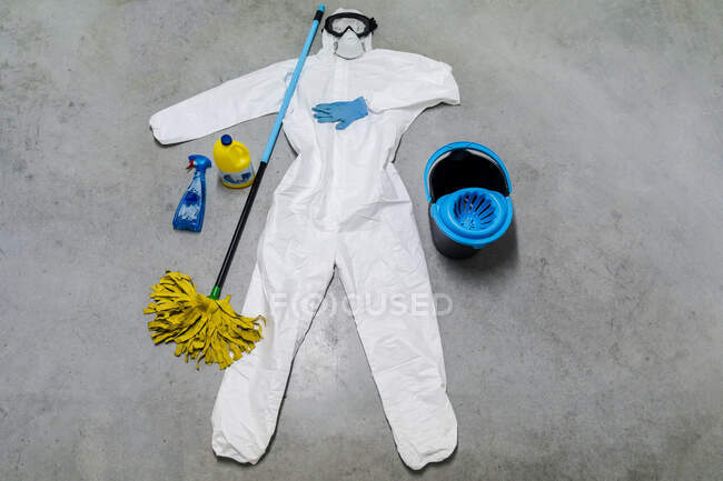 Protective clothes, cleaning agents, bucket and sanitizer lying on floor — Stock Photo