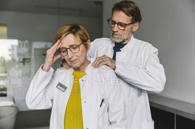Médico masajeando hombro de un colega - foto de stock