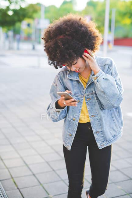 Jovem com penteado afro usando smartphone e fones de ouvido na cidade — Fotografia de Stock