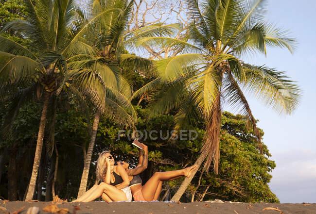 Dos mujeres leyendo un libro en la playa, Costa Rica - foto de stock