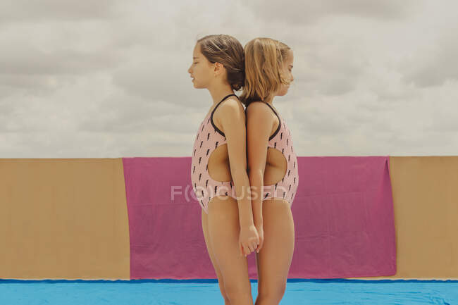 Two girls wearing swimsuits standing back to back with eyes closed outdoors — Stock Photo
