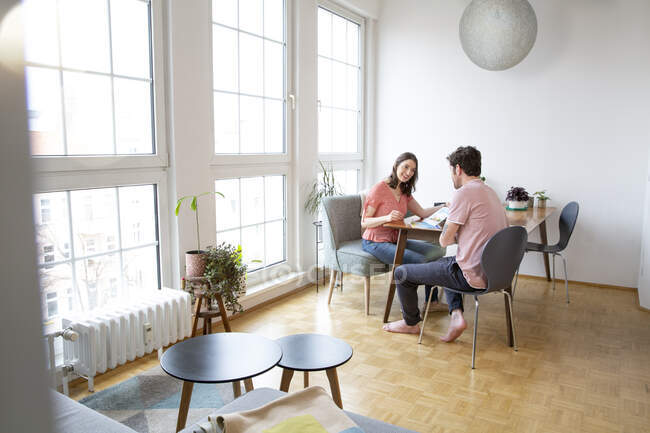 Пара сидящих за столом, разговаривающих дома — стоковое фото