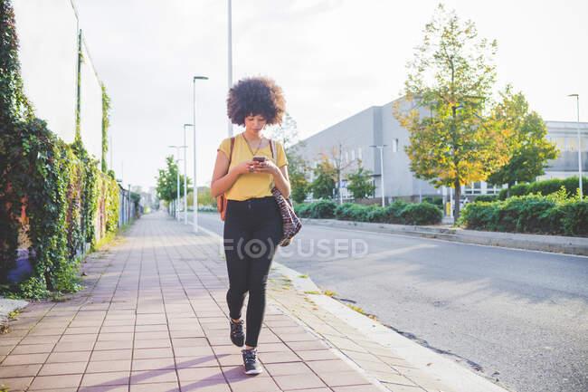 Молода жінка з африканською зачіскою користується смартфоном у місті. — стокове фото