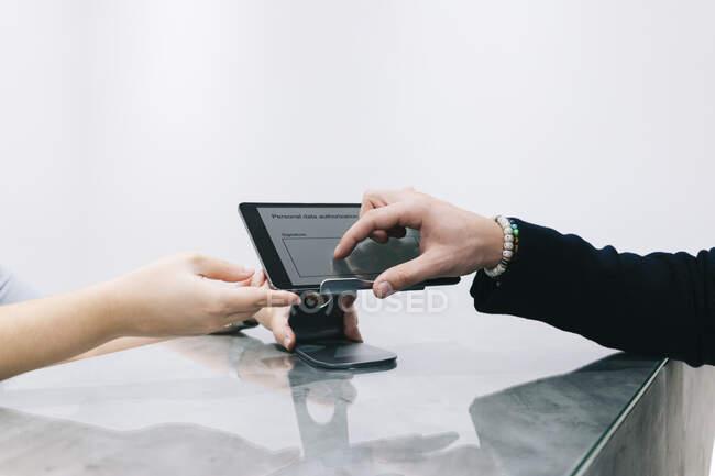 Primer plano del hombre en el mostrador de recepción de una consulta médica utilizando un dispositivo digital - foto de stock