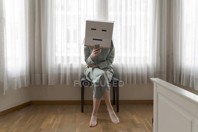 Mujer con una caja de cartón en la cabeza con una sonrisa aburrida sentada en la silla y usando un teléfono inteligente - foto de stock