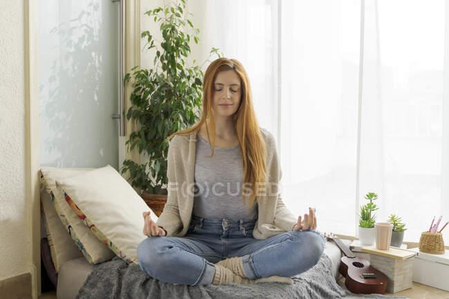 Молодая женщина практикует йогу дома — стоковое фото
