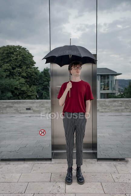 Portrait de jeune homme sérieux avec parapluie, Kassel, Allemagne — Photo de stock