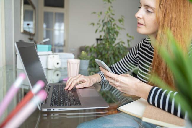Молодая женщина, использующая ноутбук и смартфон на рабочем столе дома — стоковое фото