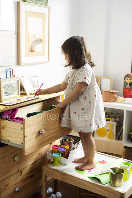 Full length of girl drawing at cabinet while standing on table in house — Stock Photo