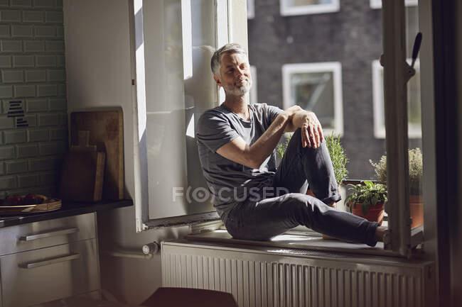 Sonriente hombre maduro sentado en la ventana en casa - foto de stock