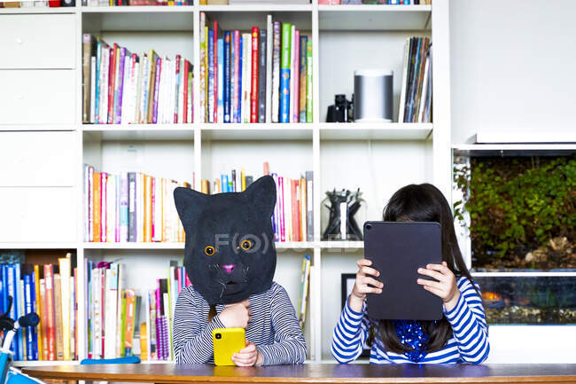 Two girls sitting at table, hiding behind digital tablet and cat mask — Stock Photo