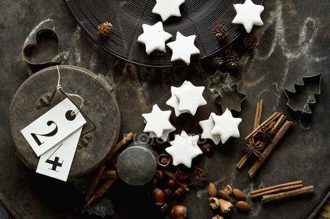 Лист для випічки русів, палички кориці, зірки різдвяні печива, кусачки печива, горіхи та металеві сувенірні коробки. — стокове фото