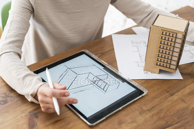 Woman working on architectural model and digital plan on desk in office — Stock Photo