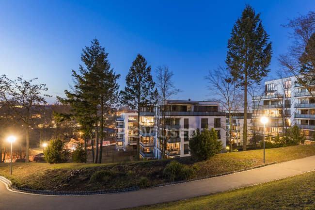 Germania, Baden-Wurttemberg, Stoccarda, Sentiero vuoto nel parco pubblico al crepuscolo con appartamenti moderni sullo sfondo — Foto stock