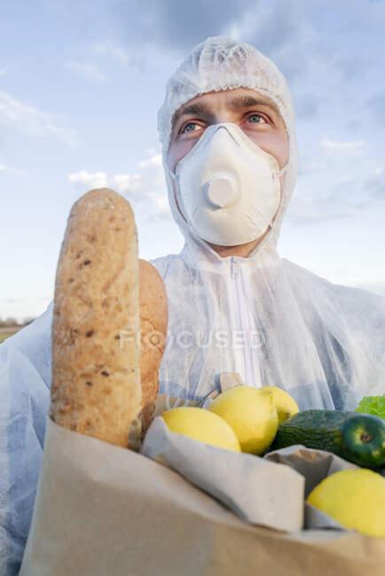 Портрет чоловіка в захисному костюмі і маска, що тримає продовольчу сумку на відкритому повітрі. — стокове фото