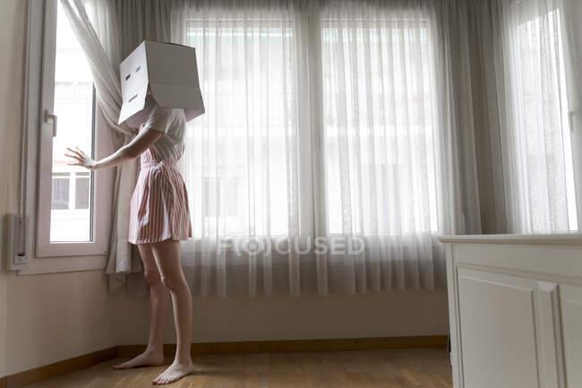Mujer con una caja de cartón en la cabeza con sonrisa aburrida mirando por la ventana - foto de stock