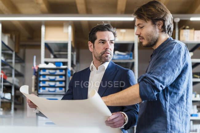 Бізнесмен і співробітник обговорюють план на заводі. — стокове фото