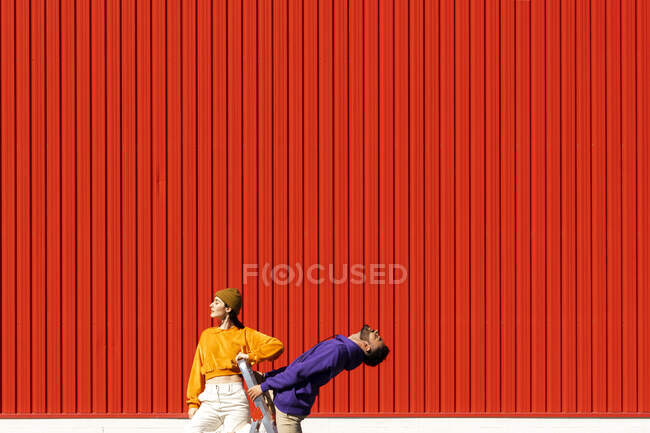 Young man and woman with a box permorming in front of a red wall — стоковое фото