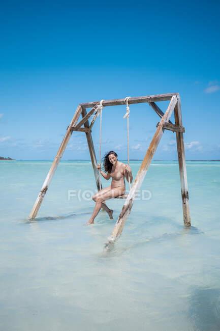 Mujer balanceándose en el mar, Bahamas, Caribe - foto de stock