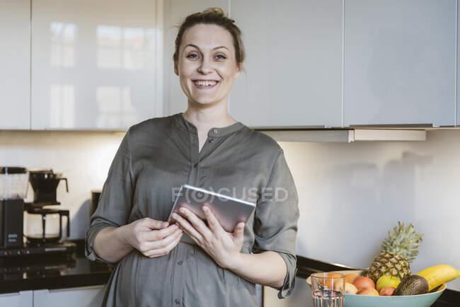 Портрет щасливої вагітної жінки з планшетом на кухні. — стокове фото